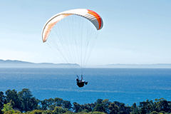 Paraglider above the Pacific Ocean. Paraglider flies over the coast of Santa Barbara, California with the Pacific Ocean in the background royalty free stock images