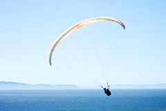 Paraglider above the Pacific Ocean. Paraglider flies over the coast of Santa Barbara, California with the Pacific Ocean in the background stock images