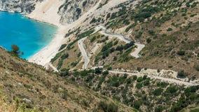 Paraglider above people enjoy the sun on the beach, Myrtos beach Kefalonia Greece royalty free stock image