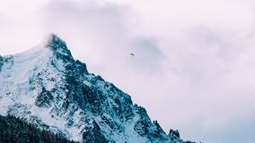 Paraglider against cloudy mountain peak Stock Photos