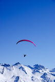 Paraglider in the Alps. Paraglider flying over the snow covered mountains in the Alps in Nidwalden, Switzerland Stock Photos