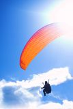 Paraglider on bright blue sky. Paraglider launching from a ridge with an orange canopy and the sun from behind. The paraglider is a silhouette and the shot is Royalty Free Stock Photos