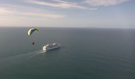 Paraglider and cruise ship in ocean. View to paraglider near cruise ship in ocean Royalty Free Stock Photos