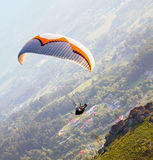 Paraglider. Descending along the slope with a colorful striped canopy - great escape Stock Images
