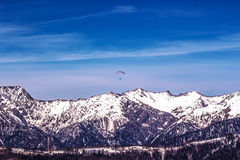 Paraglider dome in the sky above the ridge. The red dome of the paraglider in the sky above the ridge Royalty Free Stock Photo