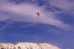 Paraglider dome in the sky above the ridge. The red Dome of the paraglider in the blue sky over snowy mountain ridge Royalty Free Stock Photo