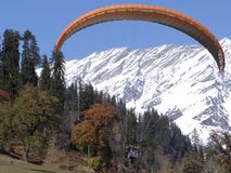 Paraglider is enjoying his ride in the snow covered mountain range in INDIA royalty free stock images