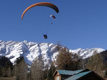 Paraglider is enjoying his ride in the snow covered mountain range in INDIA stock images