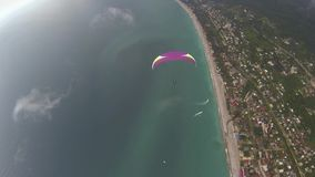 Paraglider flies along the sea and mountains stock video footage