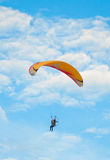 Paraglider flies in the blue sky Royalty Free Stock Image