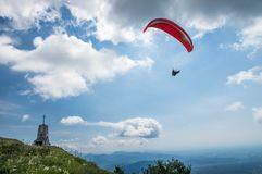 Paraglider flies over the hills with a beautiful church on a sunny day Royalty Free Stock Photo
