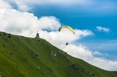 Paraglider flies over the hills with a beautiful church on a sunny day Stock Photo