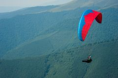 A paraglider flies over a mountain valley on a sunny summer day. Stock Images