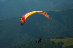 A paraglider flies over a mountain valley on a sunny summer day. Stock Photography