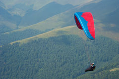 A paraglider flies over a mountain valley on a sunny summer day. Royalty Free Stock Photography
