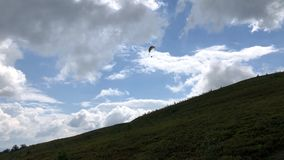 Paraglider flies over the slope of the mountain. Paraglider flies over the slope of the mountain against the sky with clouds stock video footage