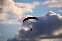 Paraglider flies in stormy skies stock images