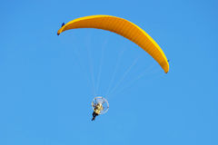 Paraglider. Flight on a motorized paraglider. Yellow paraglider with a paramotor Stock Photography
