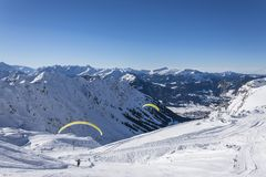 Paraglider flight in the mountains. Starting and flying paraglider in the mountains in winter Stock Photography