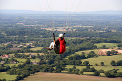 Paraglider floating. Paraglider in flight above hills and countryside Stock Photography