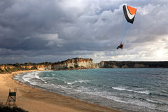 Paraglider flying above a beach Stock Images