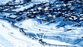 Paraglider flying above the Livigno ski resort in Italy stock photo