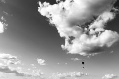 A paraglider flying against a big, deep sky, with some white clo. Uds Stock Images