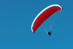 Paraglider flying in a blue sky Stock Photo