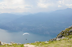 Paraglider is flying in front of mountain landscape of Alps - Mo Stock Photo