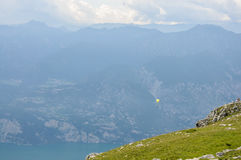Paraglider is flying in front of mountain landscape of Alps - Mo. Paraglider is flying in front of mountain landscape of Italian Alps - Monte Baldo Royalty Free Stock Images