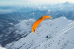 Paraglider flying over the Alps. Paraglider flying over the mountains with bright orange kite. Radial blurred motion effect applied. Unrecognizable people Stock Images