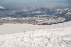 Paraglider flying over the Alps. Paraglider flying over the mountains with bright orange kite. Radial blurred motion effect applied. Unrecognizable people Stock Image