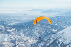 Paraglider flying over the Alps. Paraglider flying over the mountains with bright orange kite. Stunning background of the italian Alps in winter season Royalty Free Stock Photo