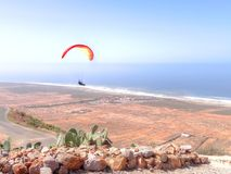 Paraglider flying over an arid coastal plain. View from the top of a mountain or sand dune across rocks and a road of a paraglider flying over an arid coastal Royalty Free Stock Photo