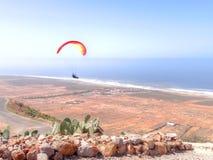 Paraglider flying over an arid coastal plain royalty free stock photo