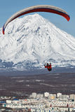 Paraglider flying over city on background of active volcano Royalty Free Stock Photography