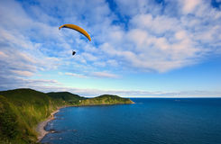 Paraglider flying over the coast. Royalty Free Stock Photo
