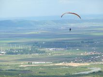 Paraglider flying over country side Stock Image
