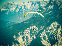 Paraglider flying over high and rugged range of Alps mountains. Cross process toned and Instagram stylized filtered stock photo with vignette Royalty Free Stock Image