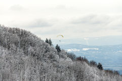 Paraglider flying over mountain. Stock Photo
