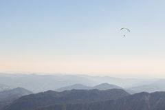 Paraglider flying over mountains Stock Images