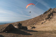 Paraglider flying over mountains Stock Photos