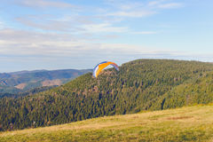 Paraglider flying over mountains summer day Royalty Free Stock Photo
