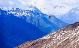Paraglider flying over mountains in the summer day sky, Paragliding recreation sport leisure activities. Swiss Alps in Zermatt. Near Mount Matterhorn Peak as a Stock Photos