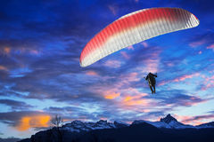 Paraglider flying over mountains in sunset Stock Photography