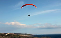Paraglider flying over the sea against the blue sky. Athlete paragliding Letty against the blue sky and sea Royalty Free Stock Image