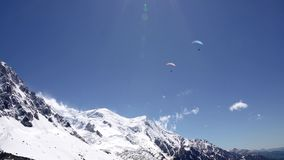 Paraglider flying over snowy mountains. paragliding against the backdrop of the monblan mountain stock video footage
