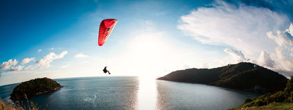 Paraglider. Flying over the water during sunset with the mountains Royalty Free Stock Images