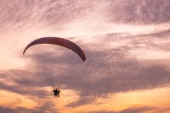 Paraglider flying at sunset Stock Photos