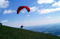 Paraglider flying in the sky. Paraglider start to jump in sky above land, on a background of mountains Royalty Free Stock Images